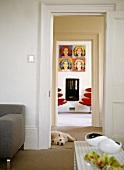 View though two doorways - living room in cool colours contrasting with bright red designer chairs below pop art picture
