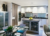 Festive, set table and central kitchen island in modern, white kitchen-dining room