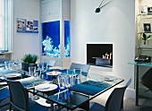 Contemporary maritime atmosphere - set glass table in front of luminous blue integrated aquarium and fire bowl in fireplace