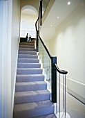 Grey runner and glass balustrade in stairwell with view of arched window