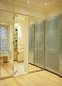 Contemporary fitted cupboards with glass and mirrored fronts and integrated door leading to ensuite bathroom