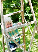 Laughing child on a wooden ladder