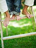 Frauenfüsse und Kinderfüsschen auf einer Leiter