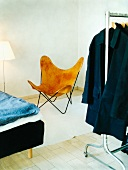 Designer chair next to bed and clothing hung on clothes rail