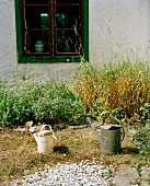 Watering can in garden in front of old house