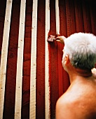 Man painting wooden house facade
