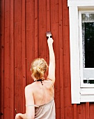 Woman painting wooden house facade