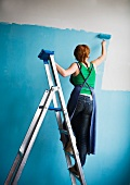 Woman on ladder painting wall with blue paint