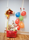 Toy box with plush toys and blown up balloons