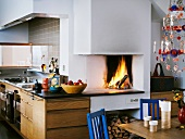 Open fireplace with fire in a modern kitchen