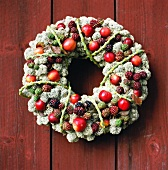 Decorative wreath with red fruit on a russet colored wooden wall