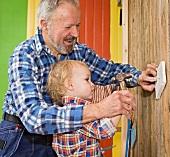 Opa und Enkel schlagen Nagel in Wand