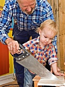 Grandfather and grandson sawing