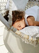 Child snuggling with pillows in a hammock