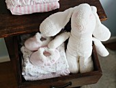 Stuffed rabbit and children's clothes in a drawer