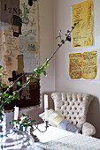 Flowering twigs and candlesticks on table in front of light reading chair in corner of living room