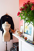 Tailor's dummy and dress hanging up in corner next to bouquet on shelf