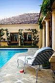 Elegant garden lounger on side of pool in grand villa complex