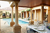 Set table on roofed terrace with colonnade and pool belonging to mansion