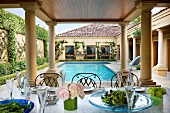 Set table on terrace with columns and pool belonging to mansion