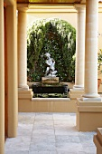 View along colonnade to ornamental fountain with stone figure