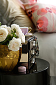 White roses in brass vase next to box with jewellery hanging of of drawers on black side table