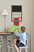 Child sitting at desk cutting craft paper