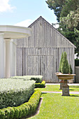 Manicured garden with cyprus trees in antique planters in front of old barn