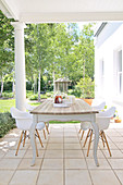 Rustic table with shell chairs on roofed, colonial-style terrace with view of garden