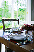 Place settings on wooden table in front of door with view of garden