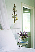 Rustic bedroom with bouquet on bedside table and view of window through open door