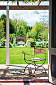 Delicate metal and linen chair on terrace with view of sunny garden