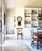 White kitchen dresser against partition in open-plan dining room of country house