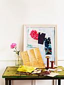 Schneideratelier - Nähutensilien auf schlichtem Arbeitstisch und Musterausschnitte auf Papier im Bilderrahmen
