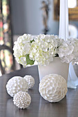 White decorative spheres with different surfaces in front of white bouquet on table