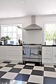 Vintage Küche mit Edelstahlherd und schwarz weißem Schachbrettboden