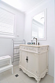 White-painted, antique cabinet in corner of white, renovated bathroom