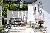 Sunny terrace with plain wooden benches against whitewashed walls