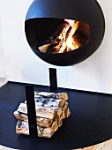 Hanging fireplace with blazing fire swinging above a pile of wood