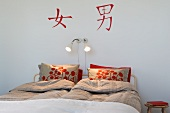 Simple bedroom with pillows made of red flowered fabric at the top end of a double bed and red Asian characters on the wall