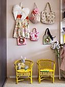 Yellow, wicker children's chairs with bags hanging on wall hooks above