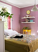 Black cat on a bed in front of a wall covered with violet, striped wallpaper