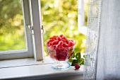 Glass dish with red jelly fruit on a window bench