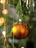 Verzierte, goldfarbene Weihnachtskugel und Lametta