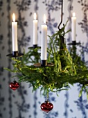 Hanging Advent wreath with burning candles and Christmas decorations