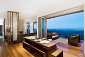 Panoramablick aus einem offenem Esszimmer durch den Balkon auf die Landschaft in Abenddämmerung