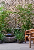 Fountain and foliage plants against stone wall