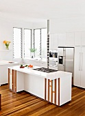 White fitted kitchen with stainless steel appliances and island counter