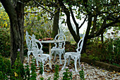Garden area with vintage style, white lacquer metal table and chairs