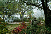 Wild garden with stone angel statue and white, vintage terrace furniture beneath pergola
